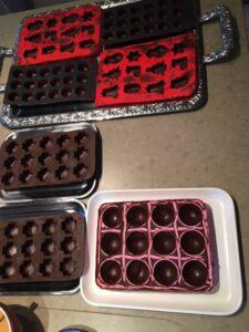 Eerste laagje chocolade in de chocoladevormen, dit vormt de buitenzijde van de praline